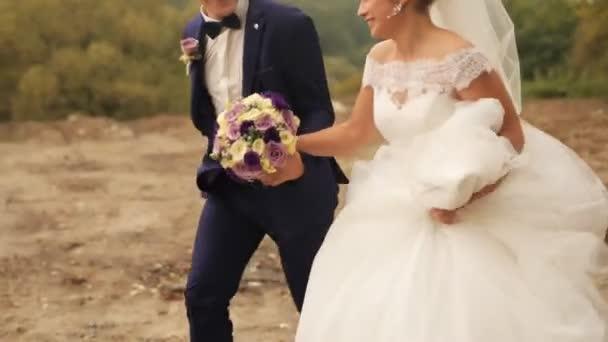 Vőlegény és menyasszony fut a parkban, a nyári nap. Esküvő házaspár. A kültéri lövés
