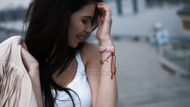 junge lachende entzückende brünette Frau, die ihr Haar berührt, lächelt, wegschaut, Lifestyle-Porträtkonzept