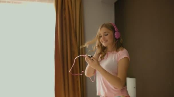 Mladá usměvavá dívka poslouchá hudbu a skákání na posteli doma