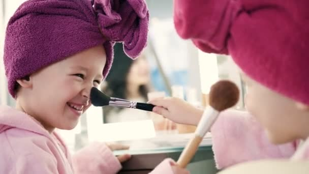 Two pretty little girls playing with make up brushes and having fun in salon. Smiling girls in pink robes