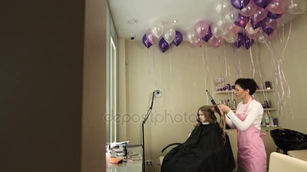 Profesionální kadeřník, kadeřnice dělat lokny na dívky, blonďaté vlasy s kulmou v salonu krásy