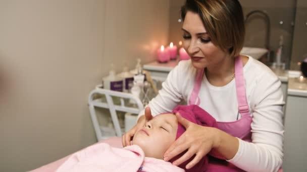 Profesionální kosmetička použití masky a dělat masáže na krásné dívky tvářičku v salonu krásy. Lázeňská léčba. Pohled na plochu