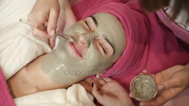 Profesionální mistr použití hlíny na ženách tvář ve spa salonu. Postup obličeje masáž v salonu krásy. Péče o obličej. Léčba. Detailní záběr