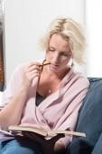 Frau auf Sofa beißt beim Lesen auf Bleistift