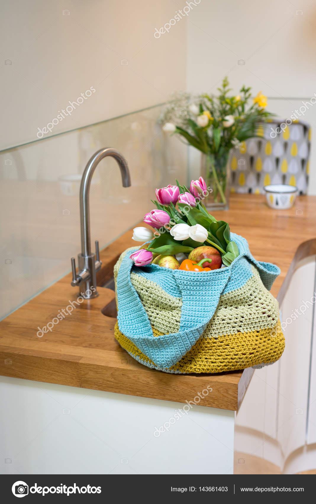 Früchte und Blumen in gehäkelte Tasche auf Küchentisch — Stockfoto ...
