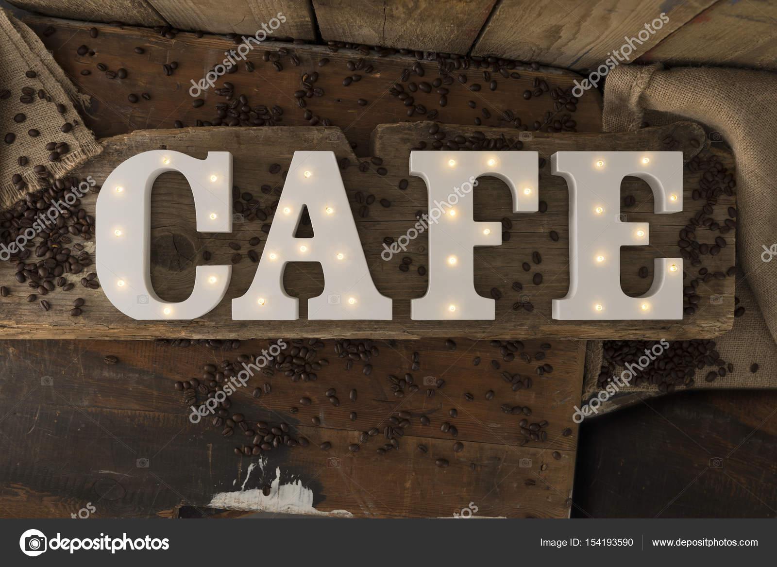 fec044eb2bf6 Διακοσμητικά γράμματα με φωτιζόμενο ενσωματωμένα φώτα Led συλλαβίζετε τη  λέξη Cafe περιβάλλεται από κόκκους καφέ ρουστίκ ξύλινα φόντο — Εικόνα από  ...