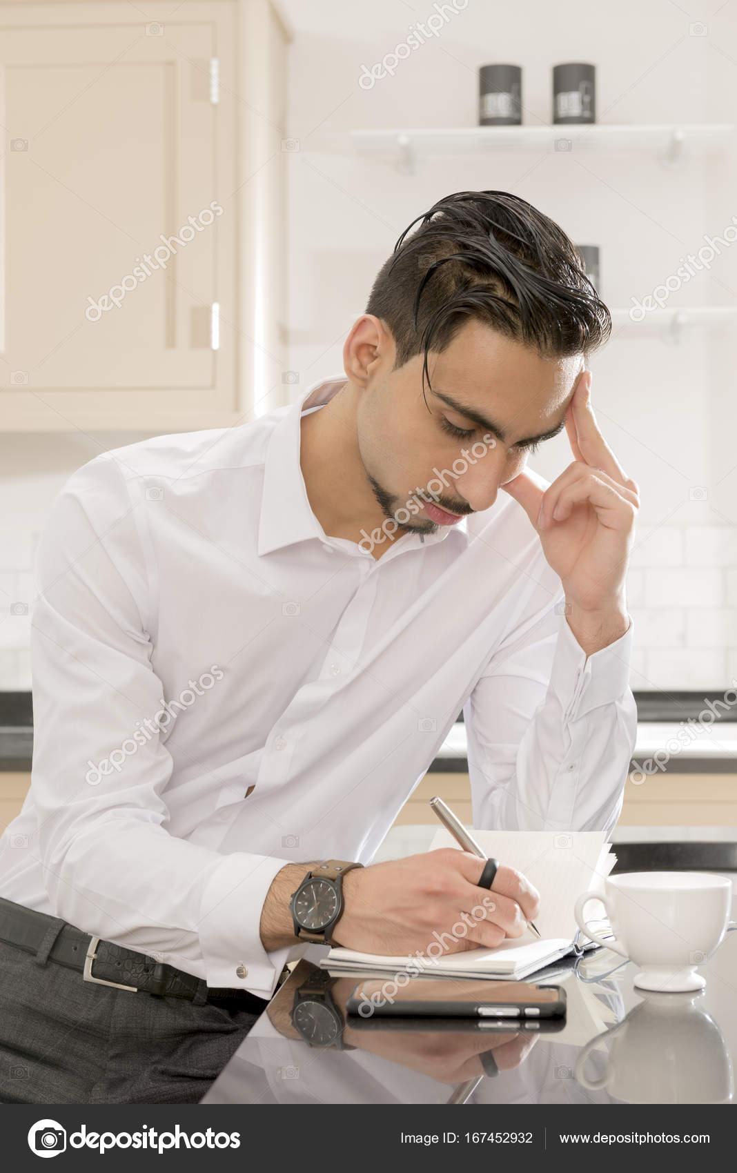 Junger Mann denken und Schreiben von Notizen in der Küche ...
