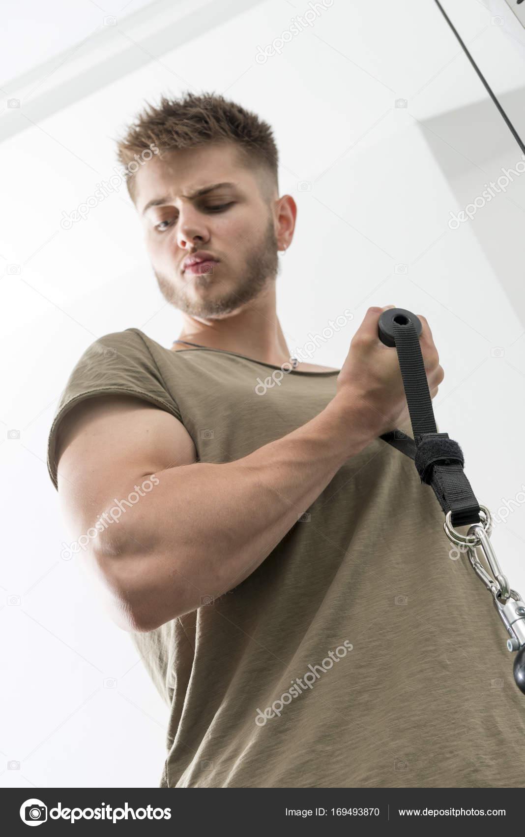 b2f854803353 Άντρας κοιτάζει επίμονα σε Bicep εκτελώντας μπούκλες με μηχανή με καλώδιο —  Εικόνα από stock photographyfirm.co.uk