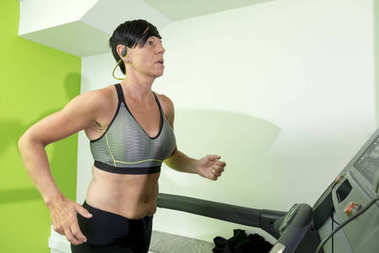 Pixie-Haired Muscular Woman Working Out on a Treadmill
