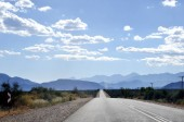 Highway Under Sunny Blue Sky with Mountain Range on Horizon