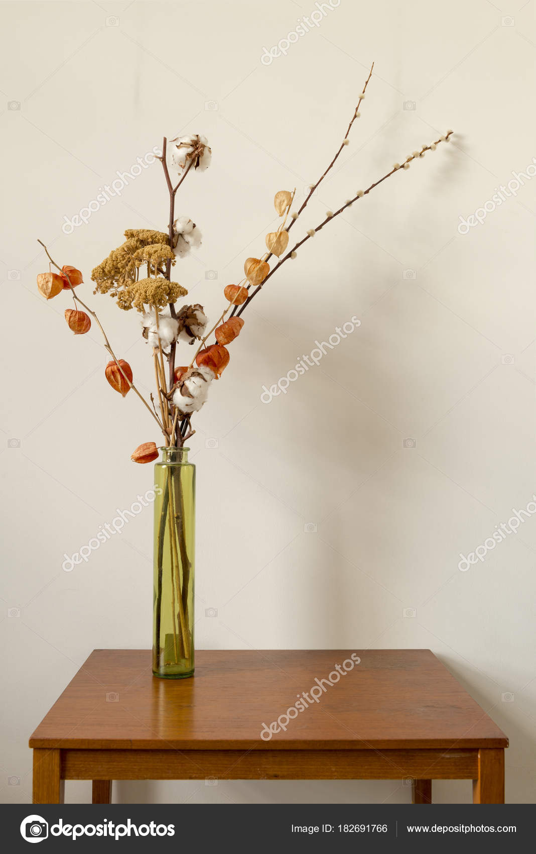 Glass Vase with Dried Flowers on a Wooden Table over White Backg ...