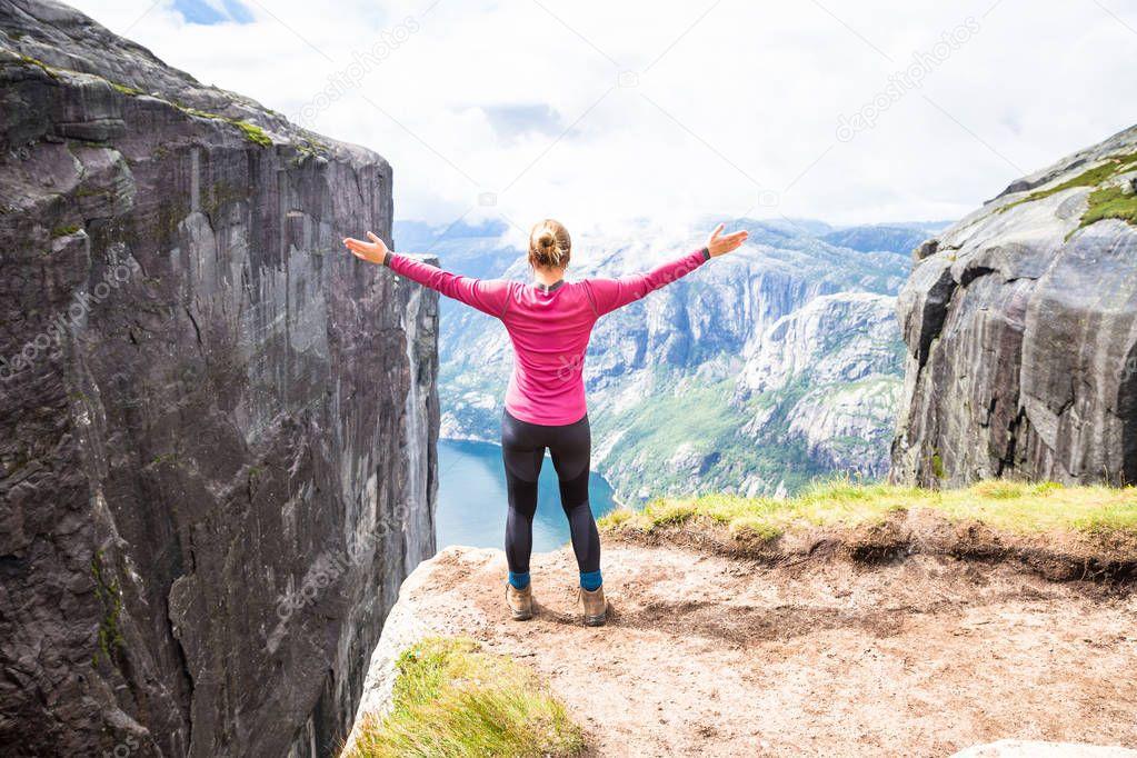 Young woman hiking on kjerag. Happy girl enjoy beautiful lake and good weather in Norway