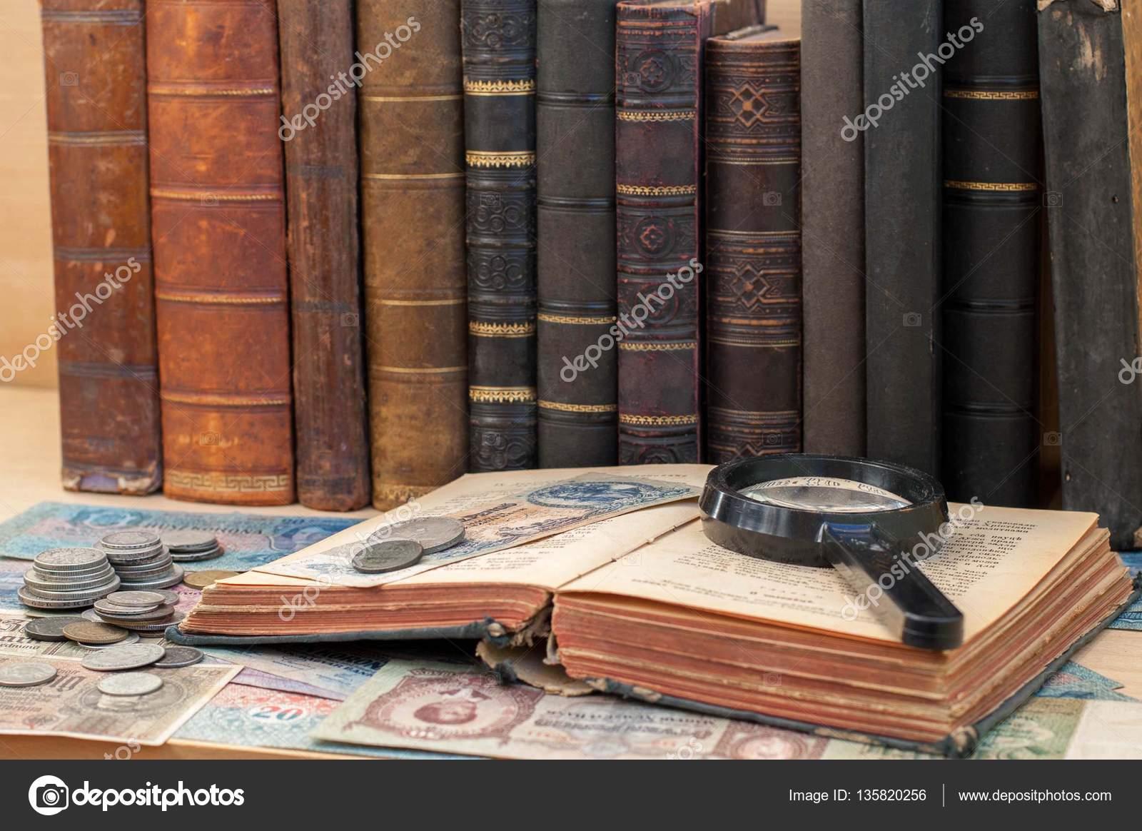 Monedas antiguas lupa y libro anticuario abierto yacen en billetes con libros antiguos en el fondo foto de siaivo