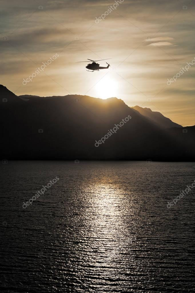 Helicopter flying over the sea at sunset