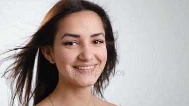 Krásné dospívající dívka s krásným streaming dlouhé vlasy úsměvy upřímně a odešle sparkes její štěstí na kameramana, byla zastřelena v Studio, zpomalené