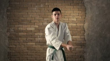 A young karateka delivering oblique chopping strike with his katana in studio