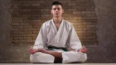 An eighteen year old sportsman in a karate kimono sits in Lotus pose and meditates