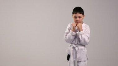 Malý karatista vlaky údery rukou, oblečený v bílé kimono a bílým páskem, ve studiu