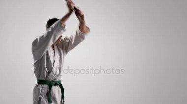 Katana využití v tréninku mladého sportovce v bílém kimonu ve studiu