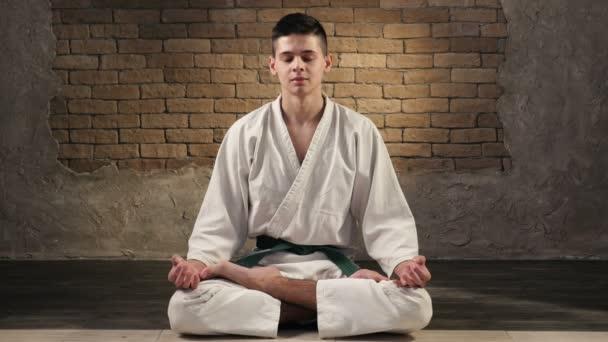 Egy tizennyolc éves sportoló kimonó sits-ban lótusz póz, és meditál