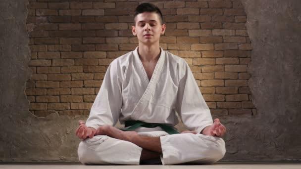 Osmnáctiletá sportovec v karate kimono sedí v Lotus pozice a medituje