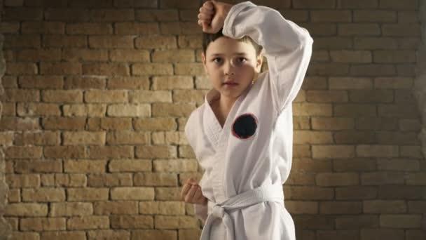 Egy kis karateka hagyományos kimonó csinál egy bonyolult önvédelmi mozgalom