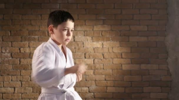 Egy fiatal karateka áll a profil, és biztosítja a közvetlen sztrájkot egy önvédelmi mozgalom