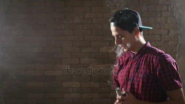 Mladý chlapec používá e cigareta a vydechne dva prstýnky najednou v slo-mo