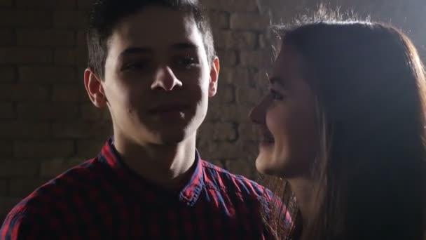 Mladá okouzlující dívka ruka tahy tváře její lásku chlapce ve studiu s cihel wal