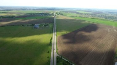 Aerial shot of a straight country highway with wide green fields lying nearby