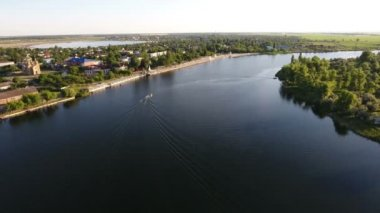 Aerial shot of the Dnipro quay with a modern road and greenary at sunset