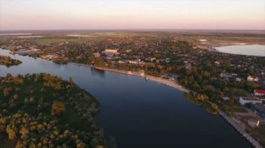Aerial shot of the Dnipro river inflows banks with houses, trees and at sunset