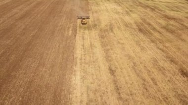 Aerial shot of a wheat field and a big tractor pulling a harrow in summer