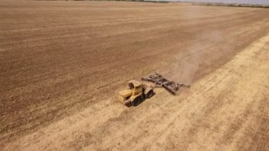 Aerial shot of a former wheat field and a big tractor pulling a harrow in autumn