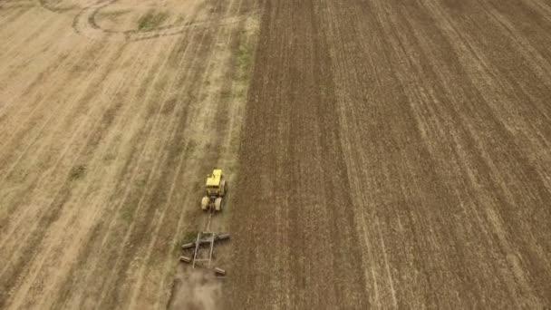 Letecký snímek pšeničné pole a traktor tahání brány v létě