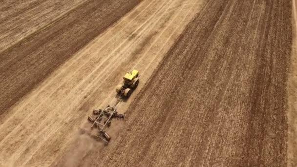 Letecký snímek pšeničné pole a silný traktor tahání brány v létě