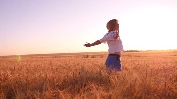 glückliche blonde Frau dreht sich um mit den Händen zur Seite auf einem Weizen, der in Slo-mo abgelegt wurde