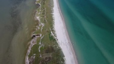 Aerial shot of a lengthy island in the Black Sea covered with a sandy road