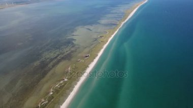 Aerial shot of an extended island with a  grimy road in the Black Sea in summer