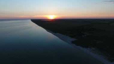 Aerial shot of a  big white sun at sunset over an island in the Black Sea