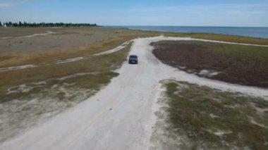 Aerial shot of a green car dashing along the sand road at the Black Sea