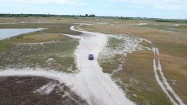 Aerial shot of a modern car driving along some sand road in Eastern Europe