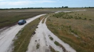 Aerial shot of a green car going along the country road at the Black Sea