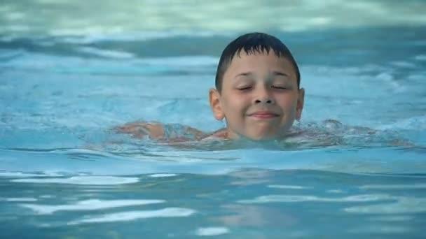glücklicher kleiner Junge mit Vergnügen planschen im Pool-Wasserpark