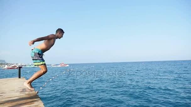 Mladý muž skočí z mola do šumivé moře Turecko resort v slo-mo