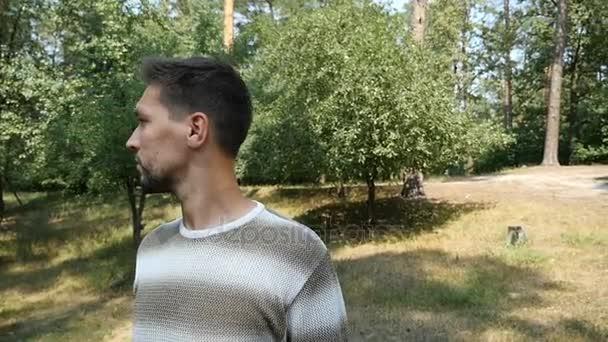 Ein junger Mann steht irgendwo auf einer sonnigen Liegewiese in einem Kiefernwald und blickt im Sommer in Zeitlupe
