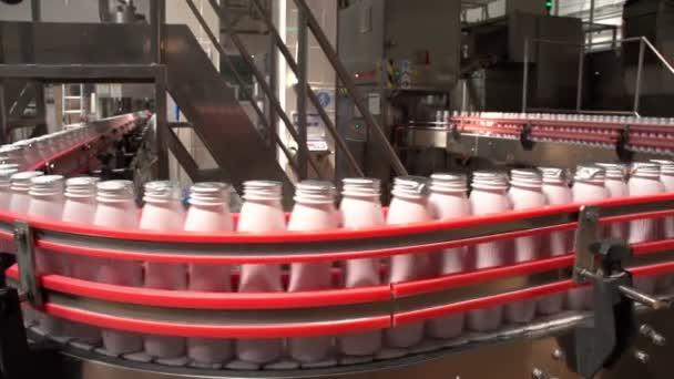 Bílý jogurt láhve v souvislé lince jezdit na trati figurativní dopravník