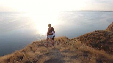 Aerial shot of a woman and her child standing on a seacoast hill with sagebrush