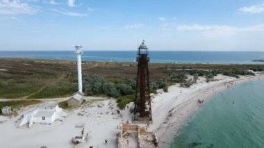 Aerial shot of white lighthouse and black tower on Dzharylhach island in summer