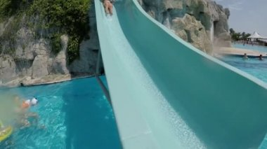 A cheerful view of a happy woman moving down a waterslide on a Turkey resort in summer in slow motion. She plunges in water with splashes..